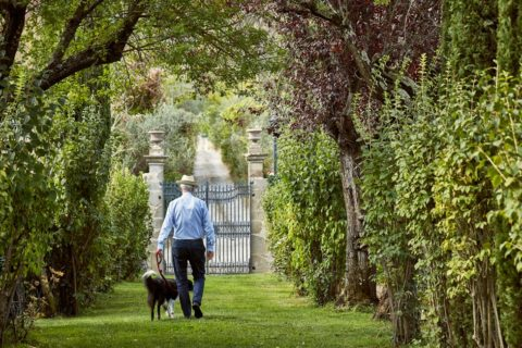 Man with dog garden Villa di Piazzano SLH Luxury Hotel Cortona tuscany